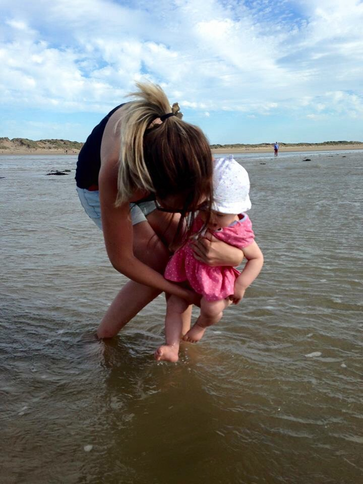 Ava having her toes dipped in the sea