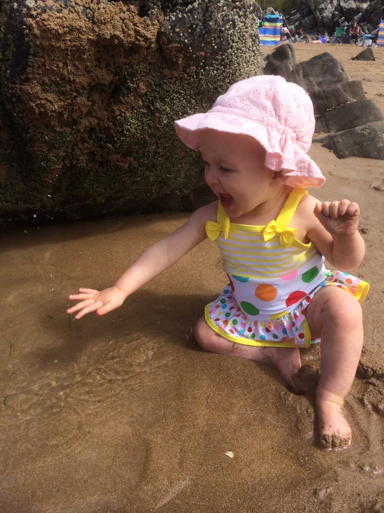 Ava splashing a beach puddle