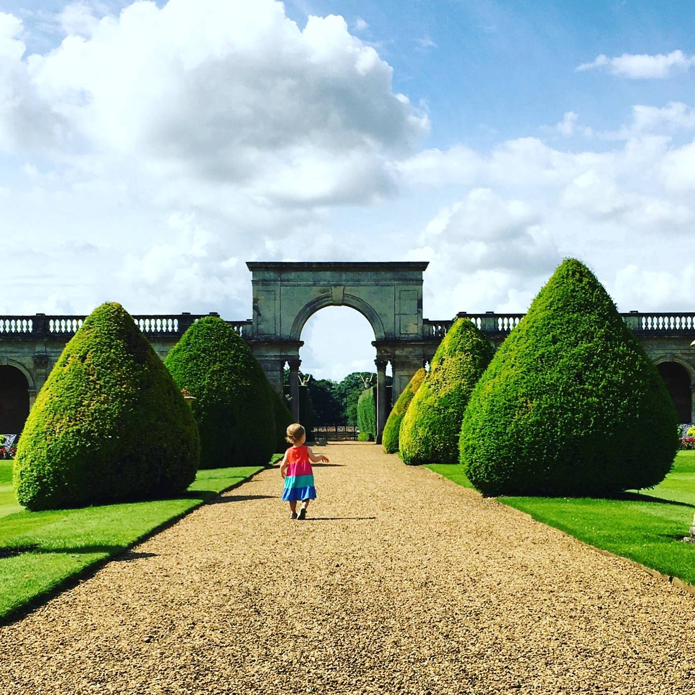 Ava running along a gravel path with greenery either side towards a beautiful stone archway