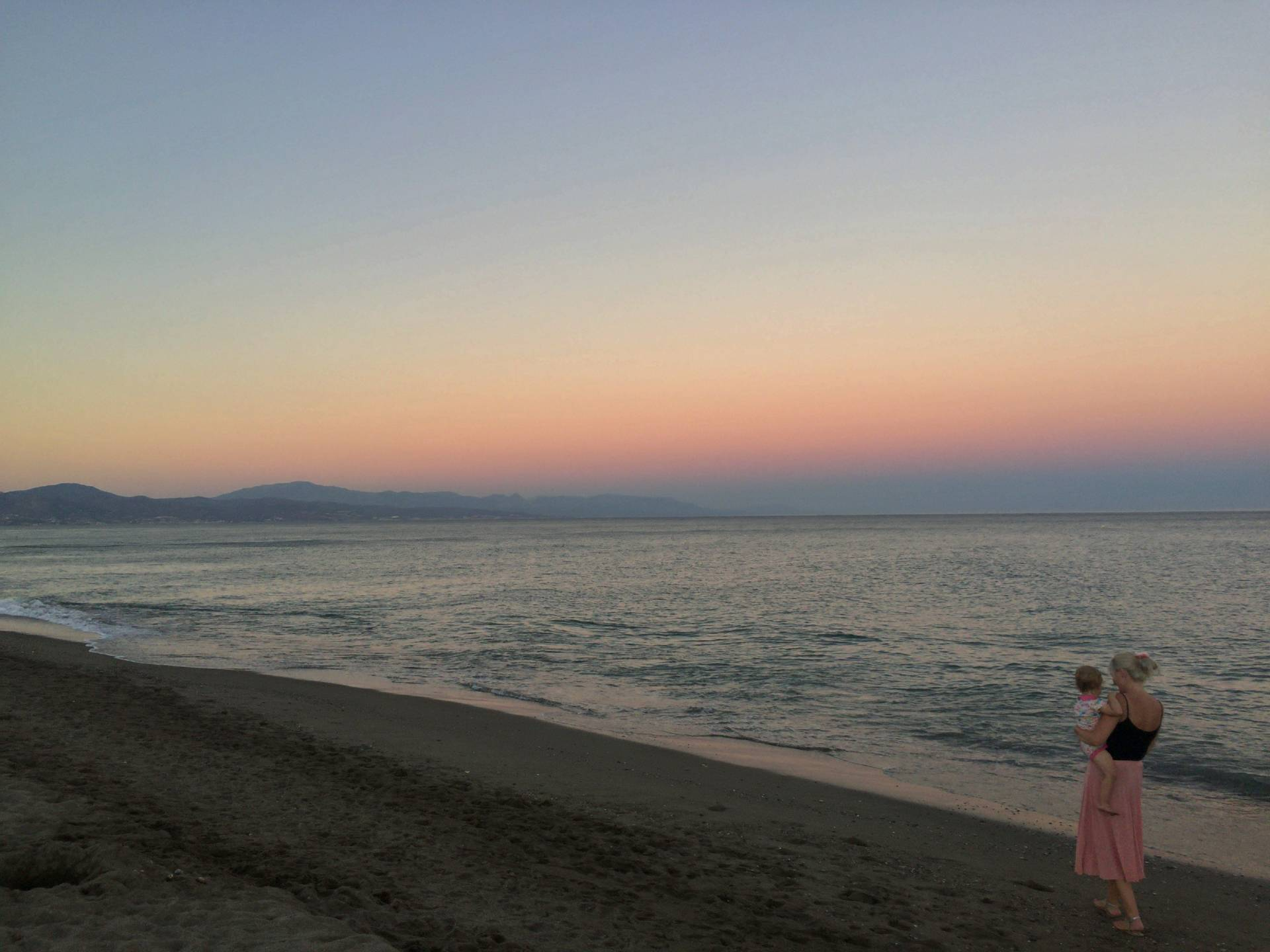 A beautiful pink sunset on the beach. Mummy carrying a toddler along the edge of the sea.